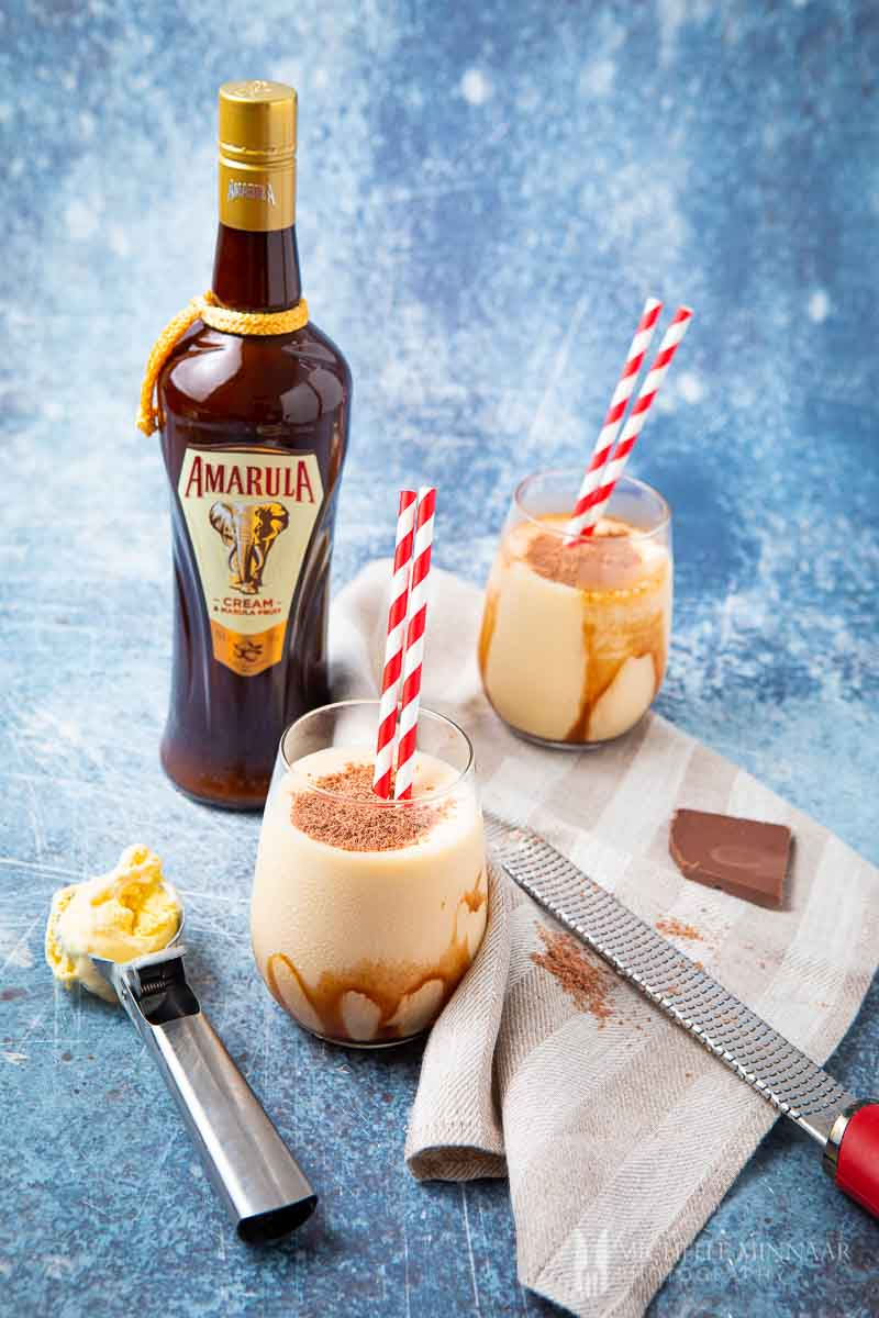 Two glasses of cream don pedro drinks with a bottle of amarula
