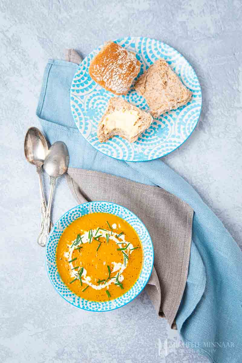 Bowl of orange slimming world butternut squash soup and rolls with buttter