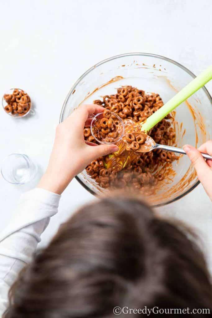 Child make balls of chocolate cheerios