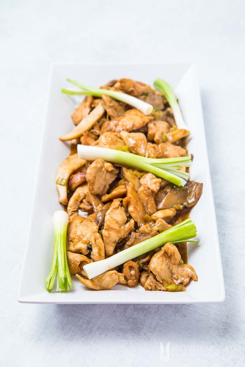 A plate of chicken in oyster sauce with leeks on it