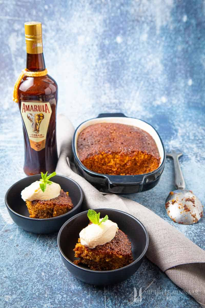 Malva Pudding in a casserole dish with a bottle of amarula