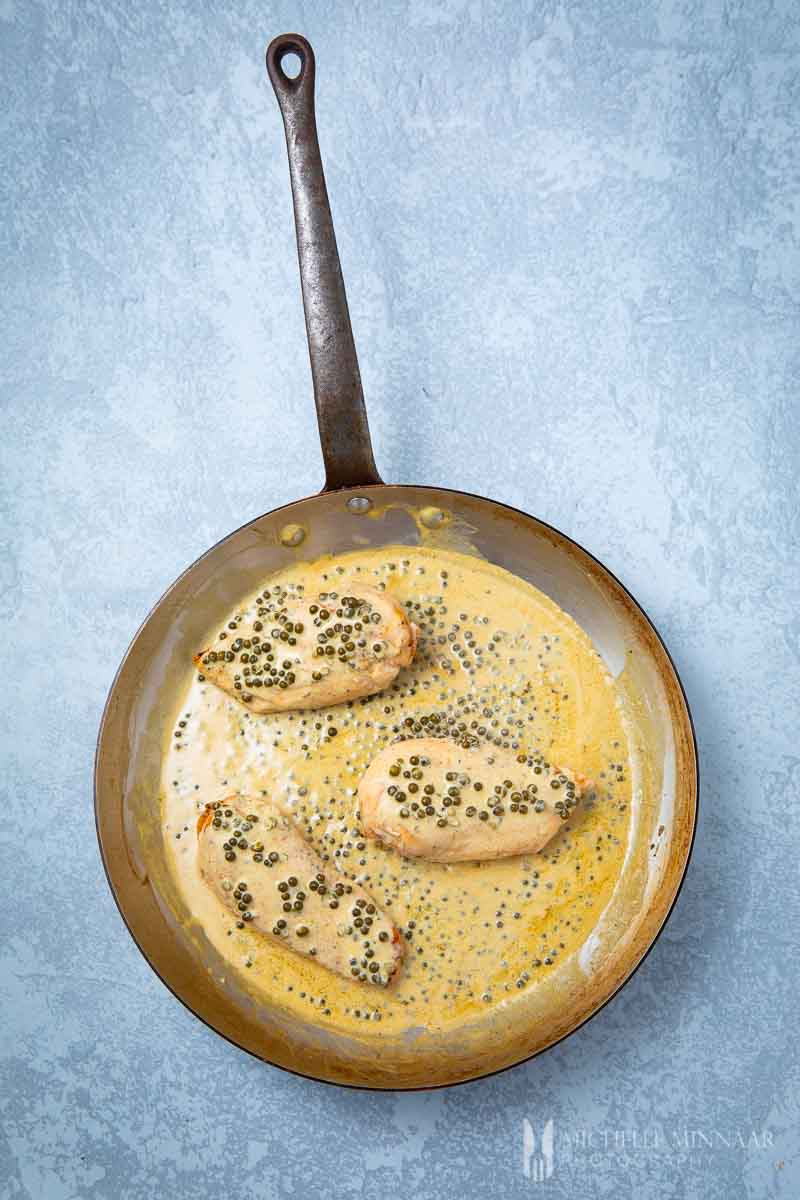 An aerial view of peppercorn chicken in a saute pan