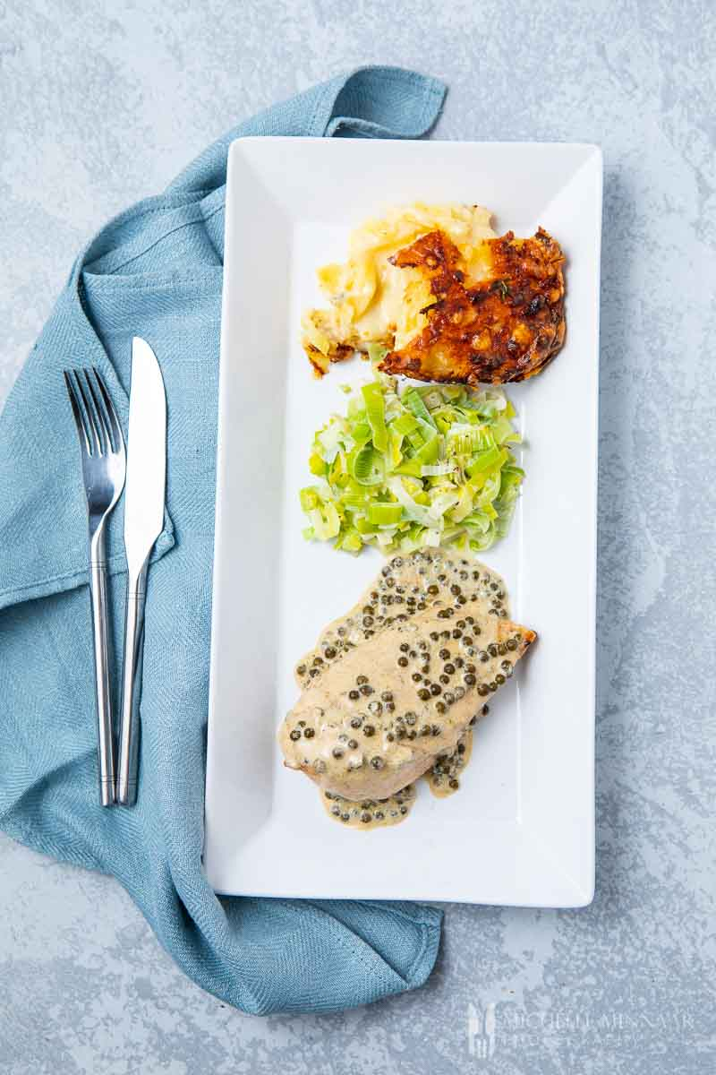 A rectangle plate with chicken, lettuce and a side dish