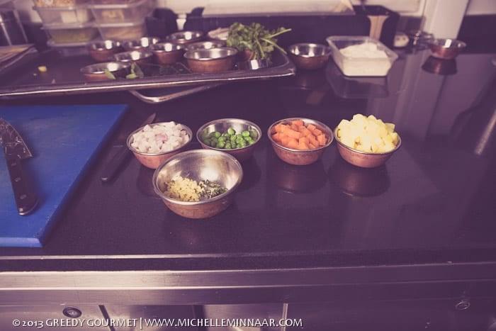 Bowlfuls of onion, ginger, carrot, potato and peas