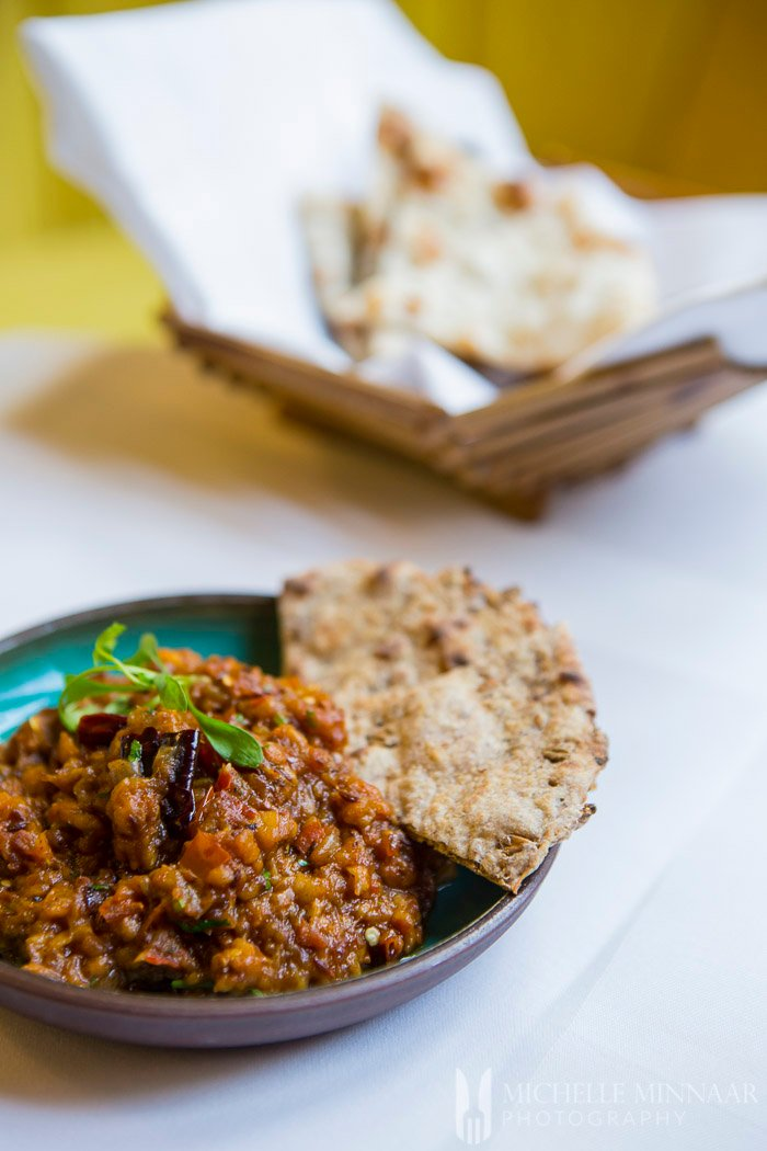 Indian side dish - mashed eggplant and naan on a plate