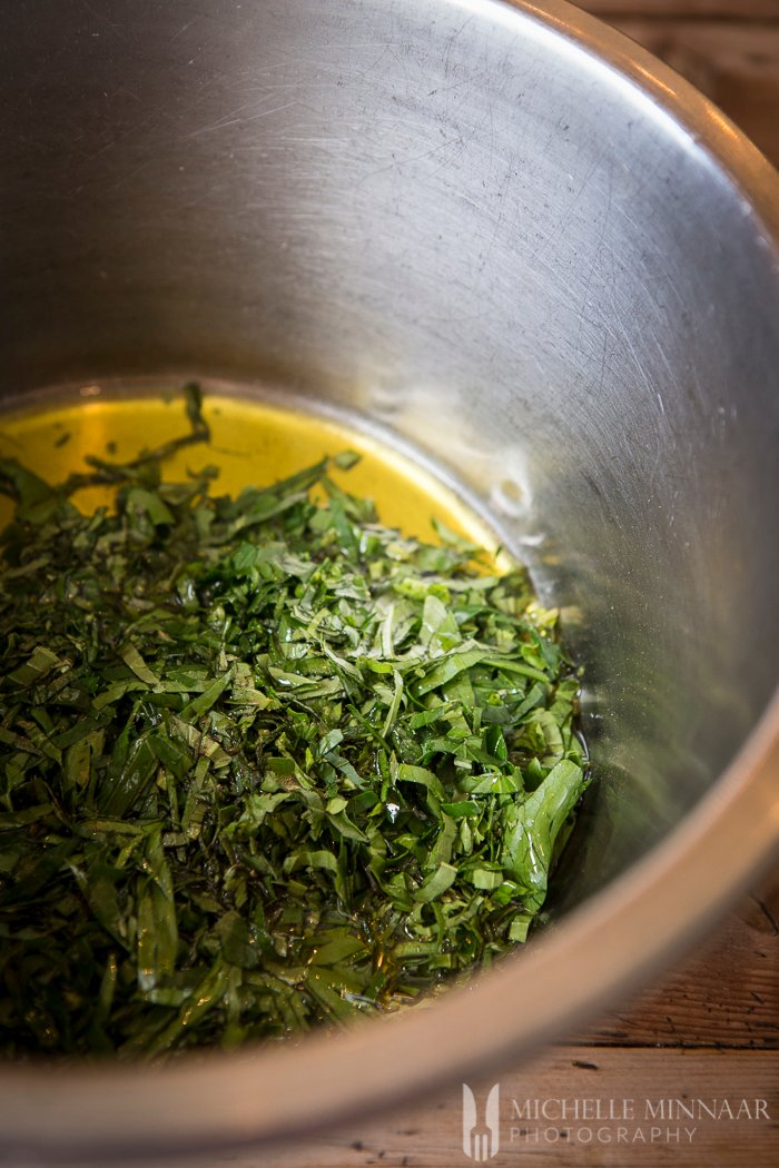 Herbs and oil in a stainless steel bowl