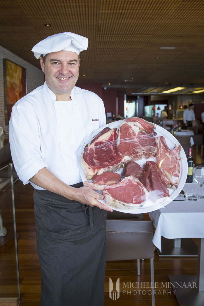 A chef holding a plate of a variety of steaks