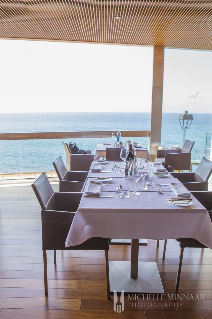 A long set dining table in Brunelli's Steakhouse with an ocean view