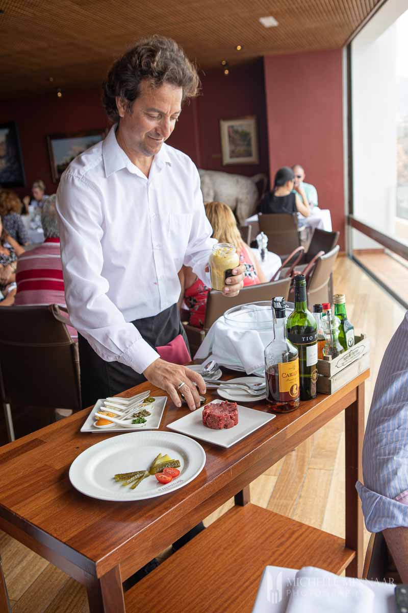 A man providing table side service for the steaks