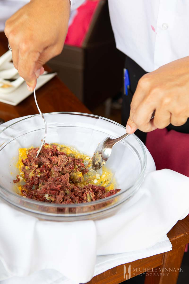 Steak tartare being prepared table side in a glass bowl