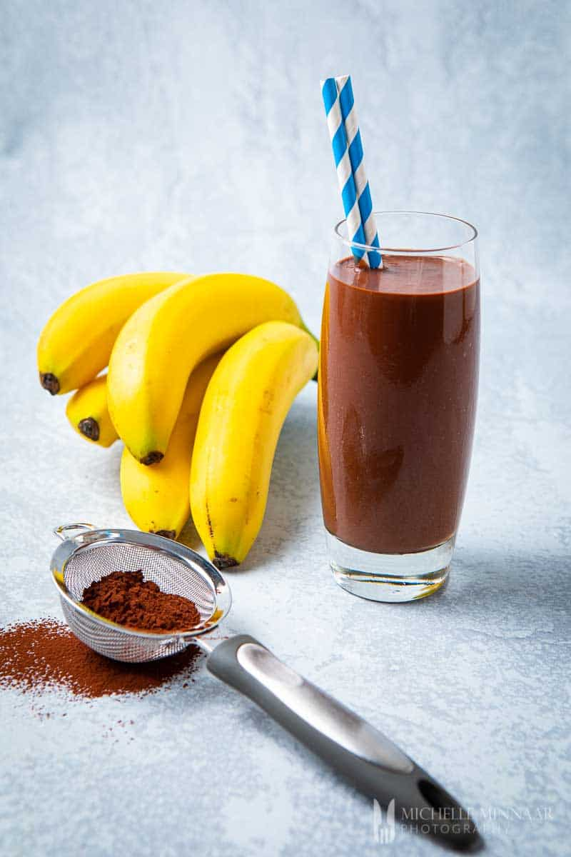 Almond Milk Protein Shake with cocoa powder and fresh banana bunch.
