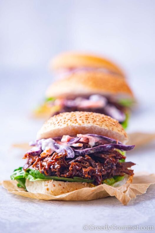 A pulled lamb slider on a seeded bun