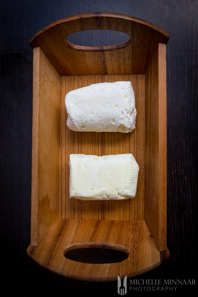 Soaked Vs Straight Halloumi cheese blocks in a wooden box