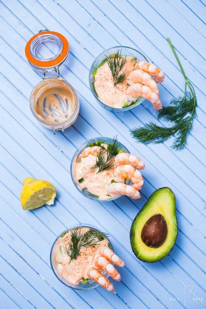 An aerial view of three prawn cocktails in glasses with a avocado and lemon