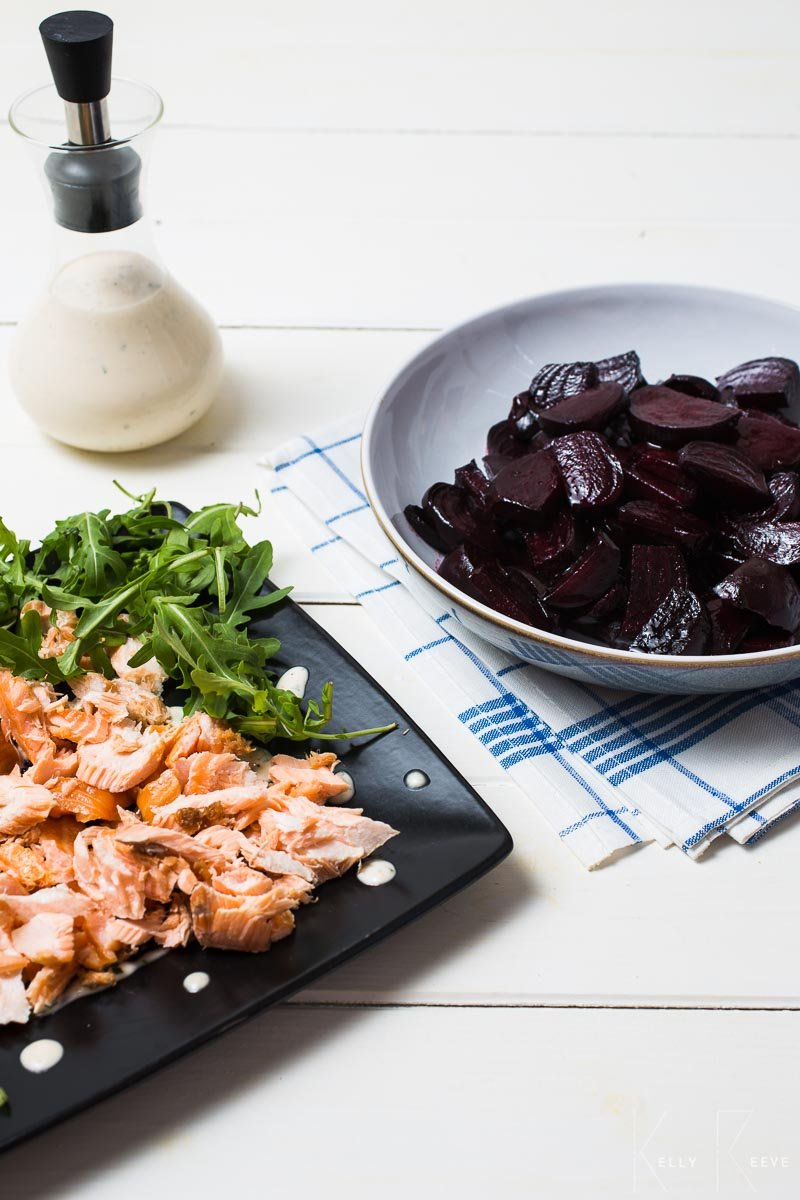 A bowl of roasted beetroot with a salmon and salad on a table
