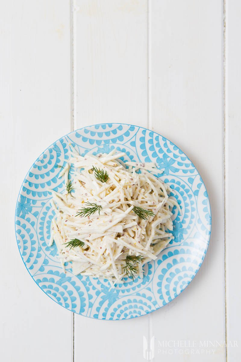 A plate of celeriac remoulade : white strips of celeriac on a blue plate in a white sauce