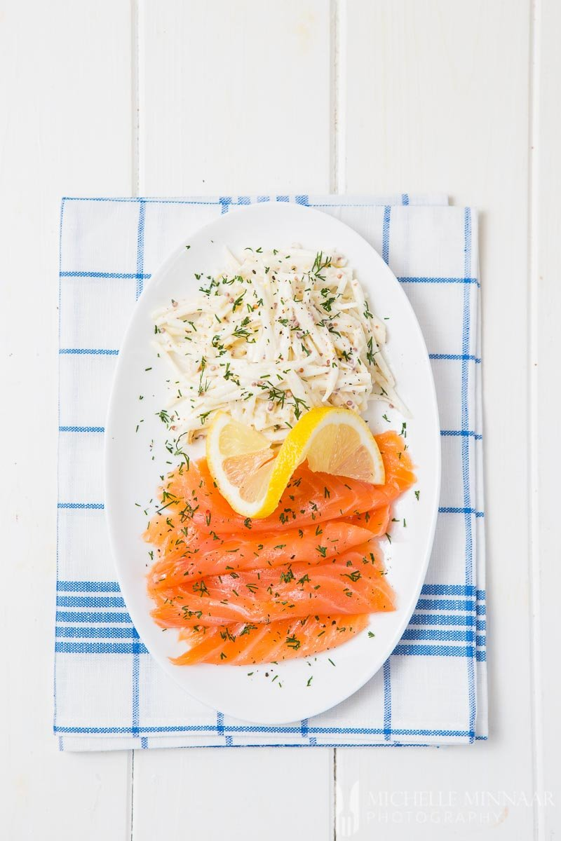 A plate of smoked salmon with a lemon on top next to celeriac remoulade