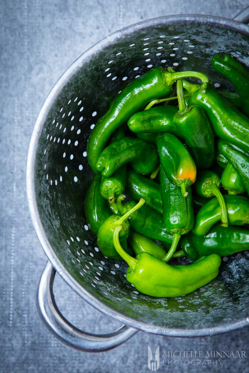 Green peppers in a strainer and washed