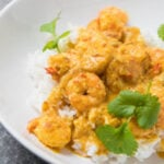 A close up view of prawns and rice in a white bowl