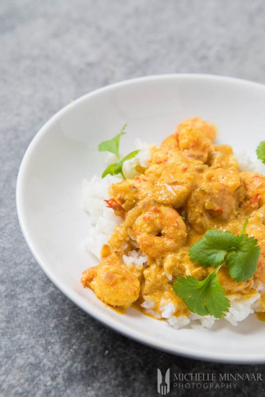 A finished bowl of Prawn Korma, prawns covered in yellow sauce on white rice