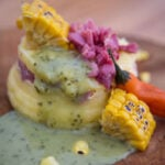 Costilla con Papa Encausada - pork potatoes corn and green sauce on a cutting board