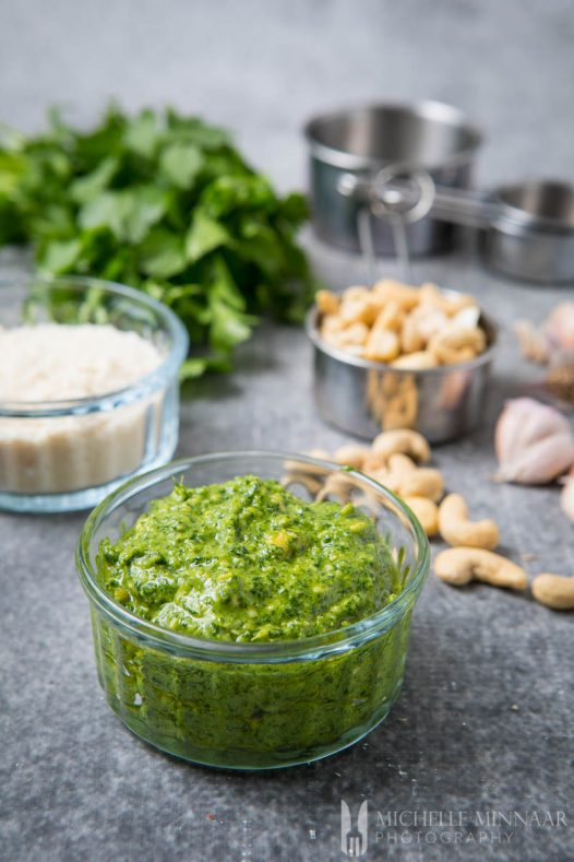 a bowl of green cashew pesto in a clear dish