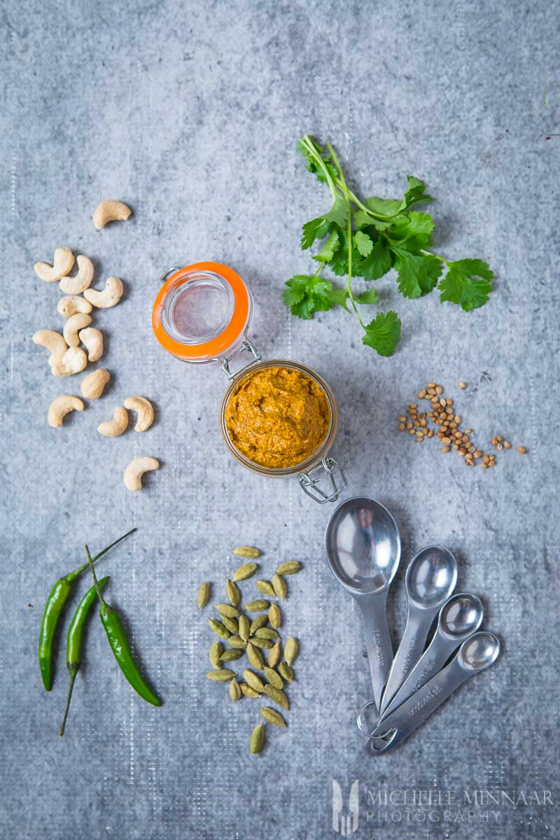 Ingredients for Korma Curry paste on a counter, spoons, cashews, paste, peppers and seeds
