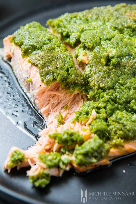 A close up of Salmon covered in pesto green sauce for Pesto Baked Salmon
