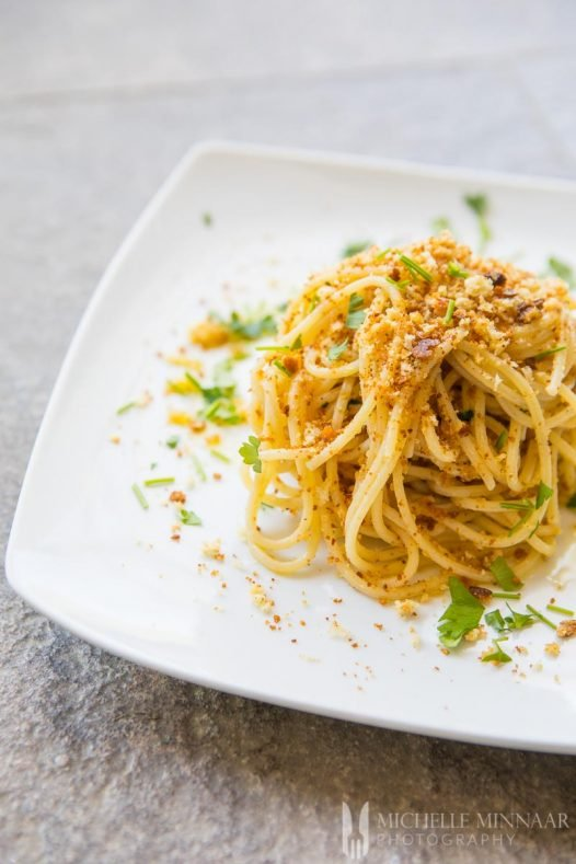 Spaghetti Alla Carrettiera - a plate of yellow spaghetti with red and green seasoning