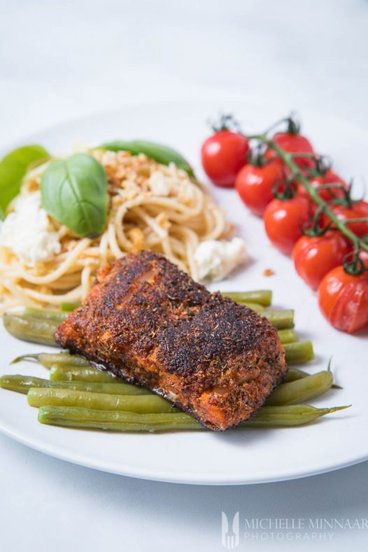 Blackened Cod - A piece of blackended fish on a bed of green beans, with a side of pasta and tomatoes