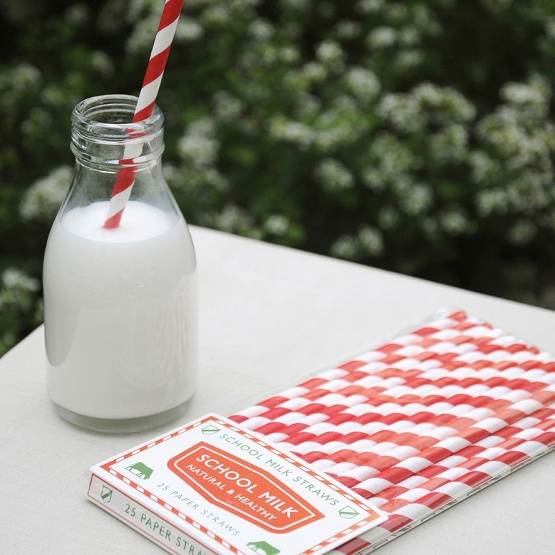 A package of red and white paper straws and a glass of milk