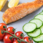 A piece of salmon, tomatoes, cucumbers and lemons for Air fried Salmon
