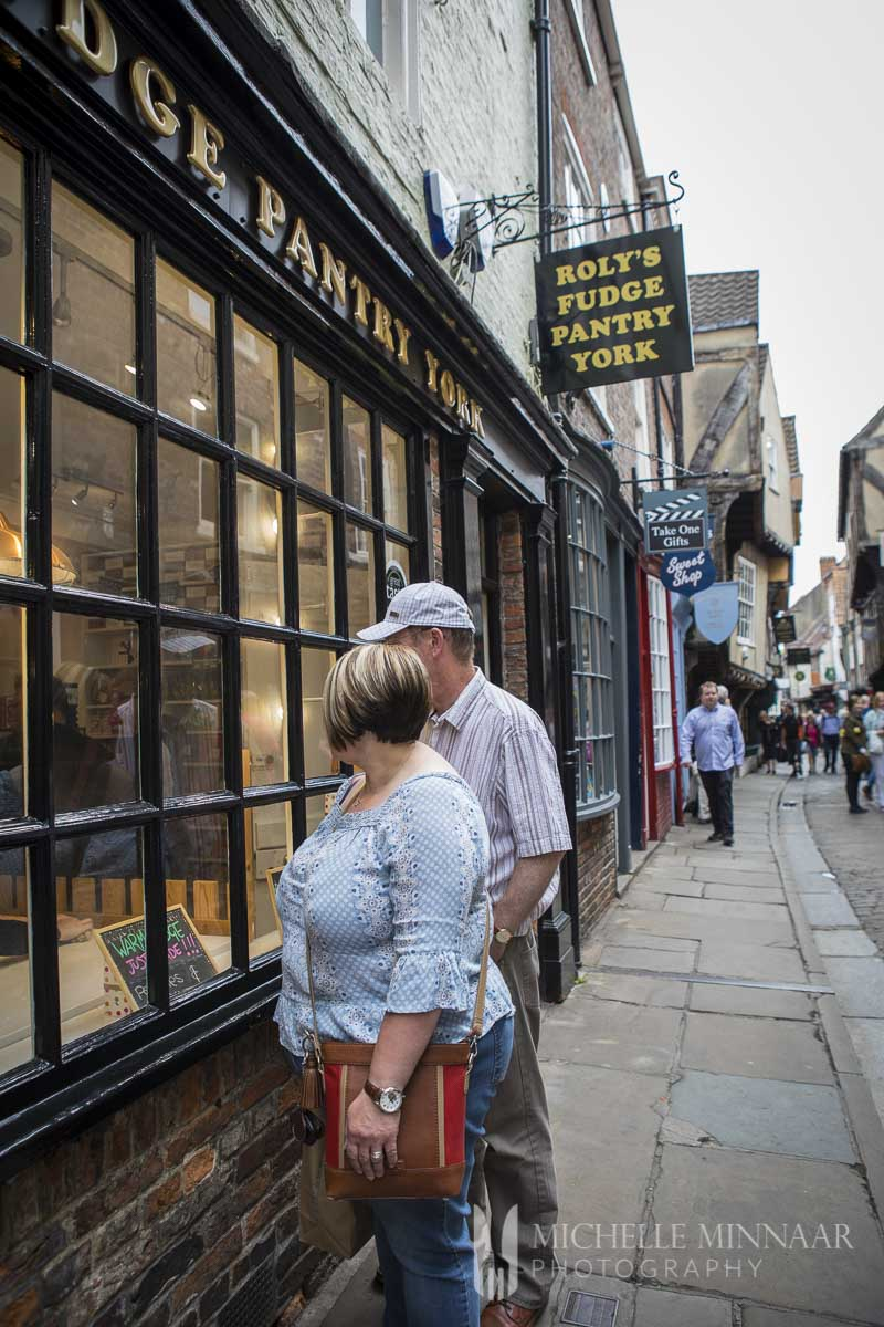 Two people looking into the window of the York Fudge location