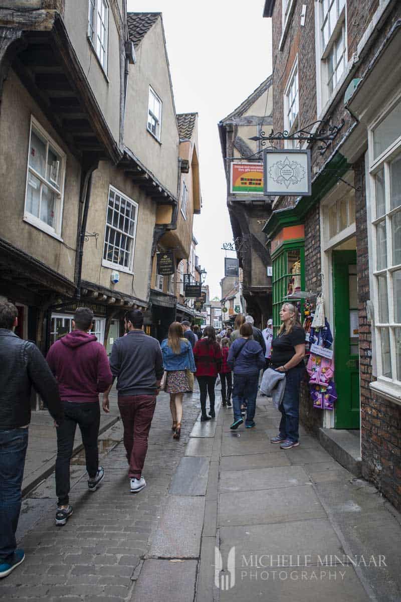 People walking down a narrow street