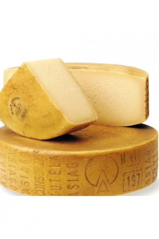 A large wheel of asiago cheese and two chuncks as a manchego cheese substitutes