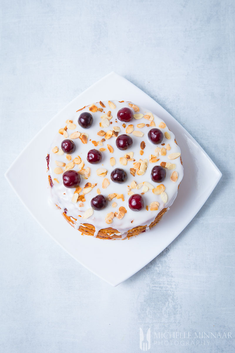 The top of the cherry bakewell cake with cherries and frosting and sliced almonds