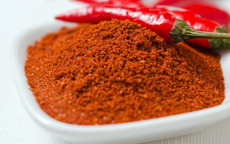 A close up of red cayenne pepper in a white bowl as a paprika substitute