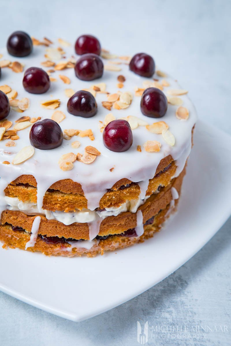 A finished cherry bakewell cake - four layers of cake with frosting drizzled on the sides and cherries on top