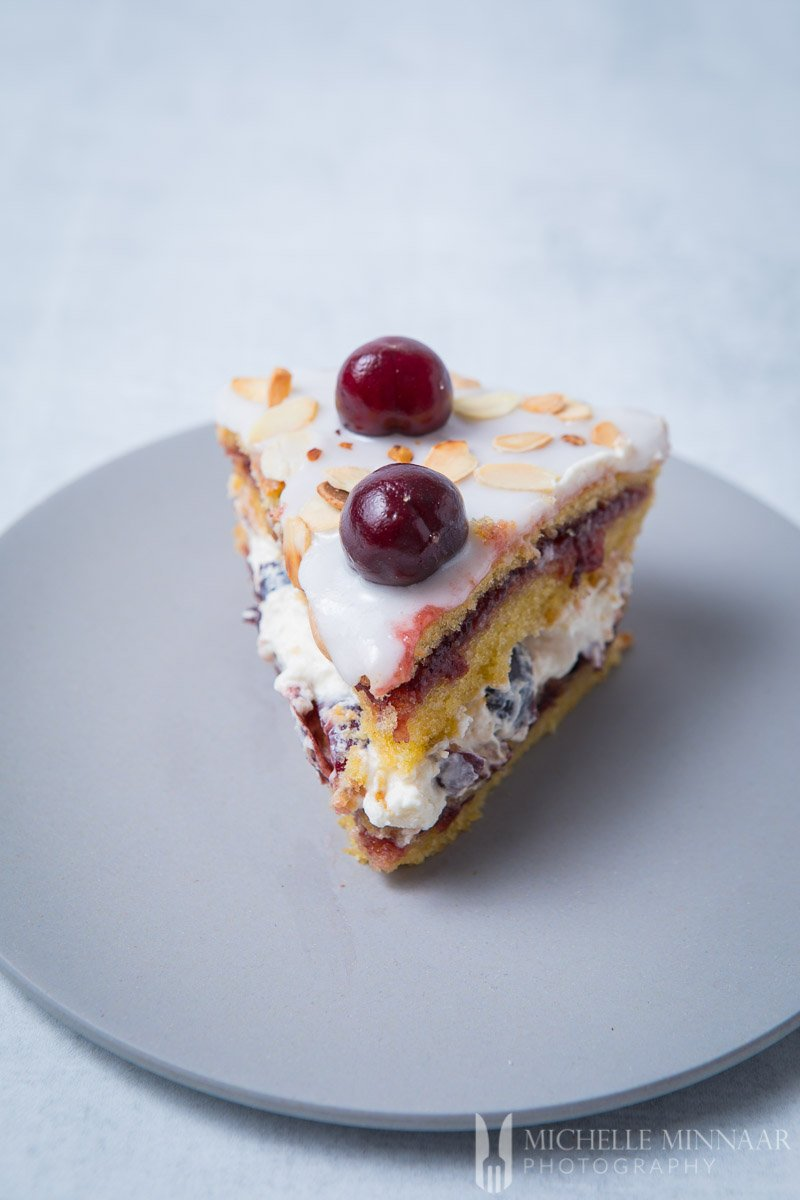 A close up of a cake slice of the cherry bakewell cake