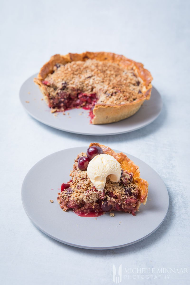 A Whole Cherry Crumble Pie and a slice taken out with a scoop of ice cream on top