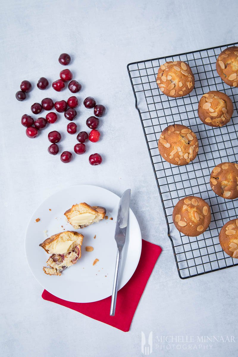 Loose cherries, muffins on a wire rack and a plate with one cherry muffin cut in half