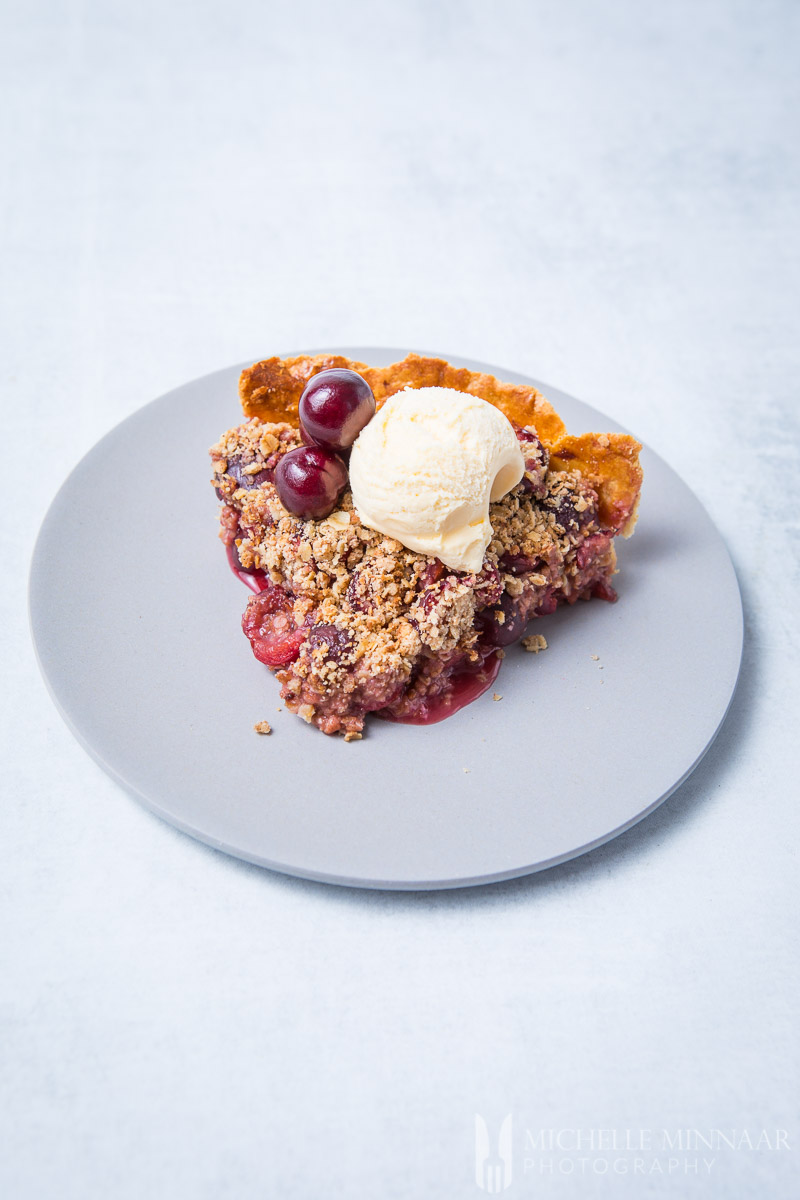 A slice of cherry crumble pie with ice cream on top