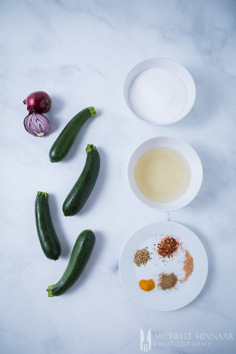 The ingredients for Courgette Pickle on a counter: Courgettes onion spices