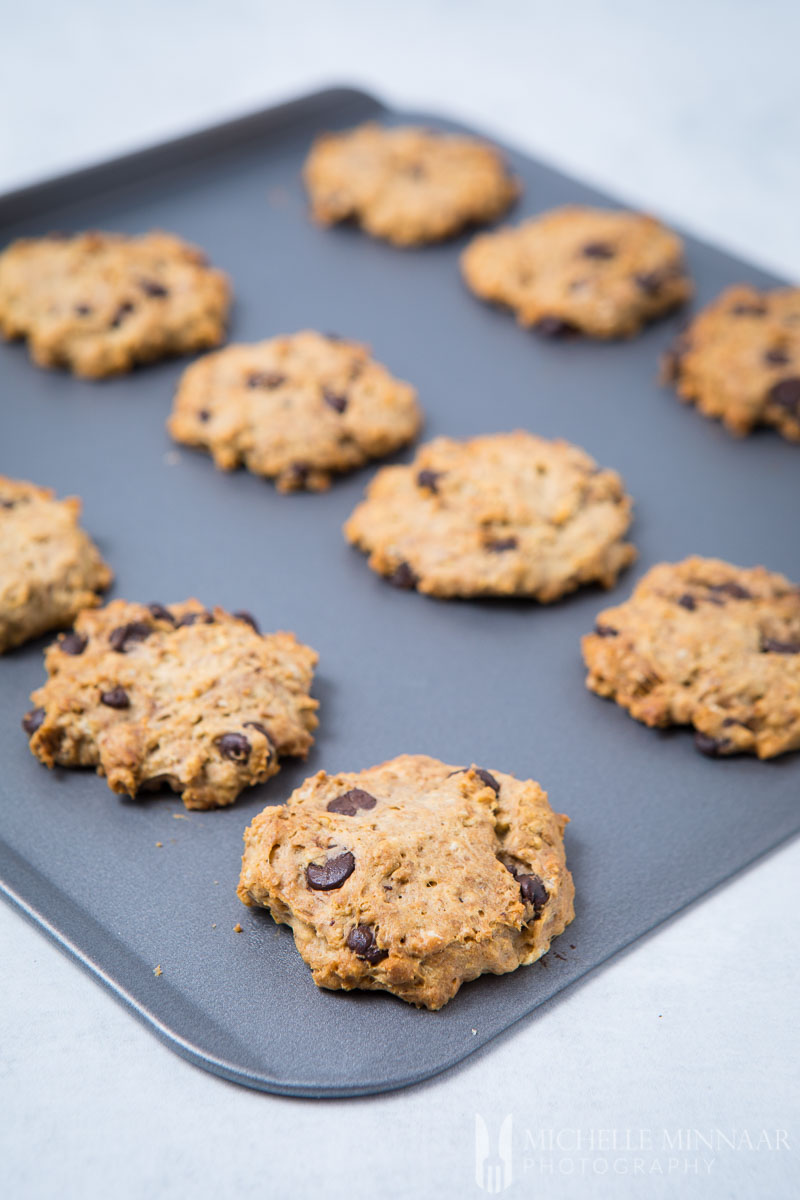 A close up of sugar free chocolate chip cookies on a sheet pan