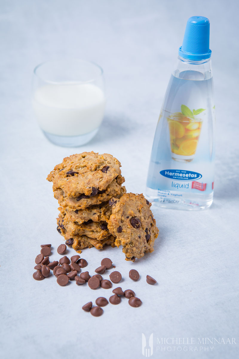 A bottle of Hermesetas liquid, a pile of sugar free chocolate chip cookies and a glass of milk