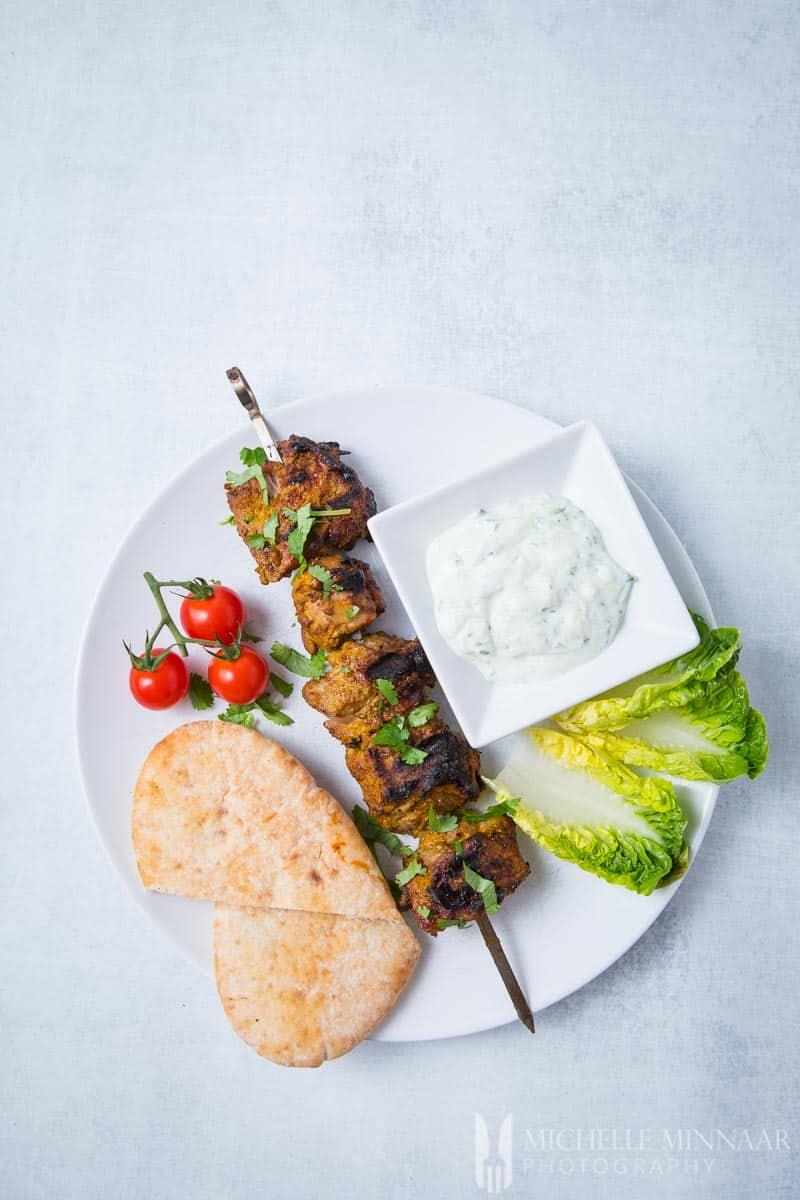 A complete meal of Lamb Tikka, Tomato, Lettuce, Lamb Skewer and yogurt dip