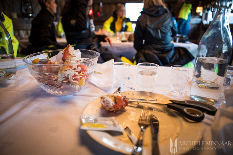 A view from the table with plates and scissors to cut open the crab leg from the King Crab Safari