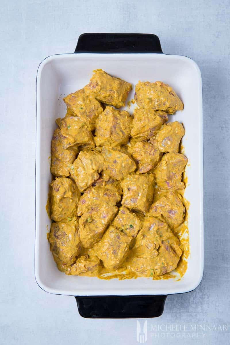 Lamb Tikka Marinating in a yellow sauce