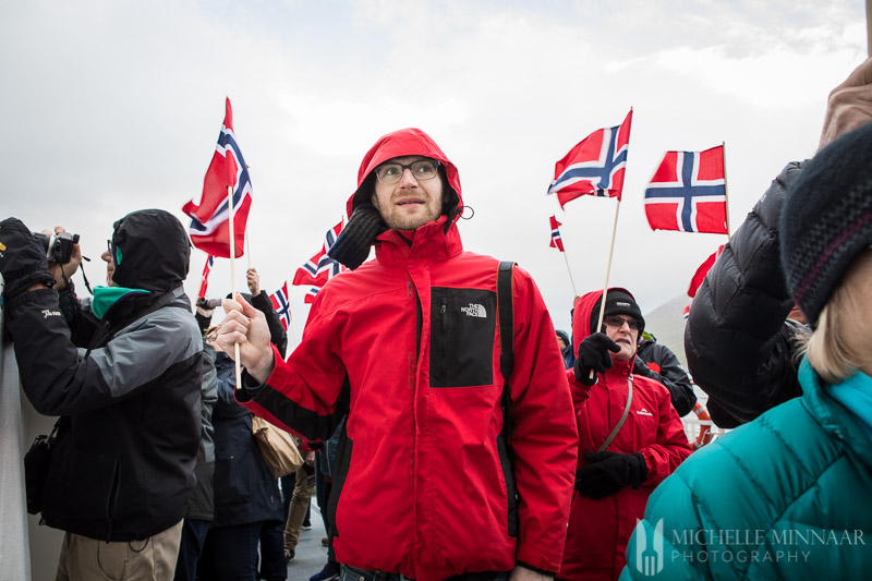 A man wearing a red jacket holding a Norweigen flag