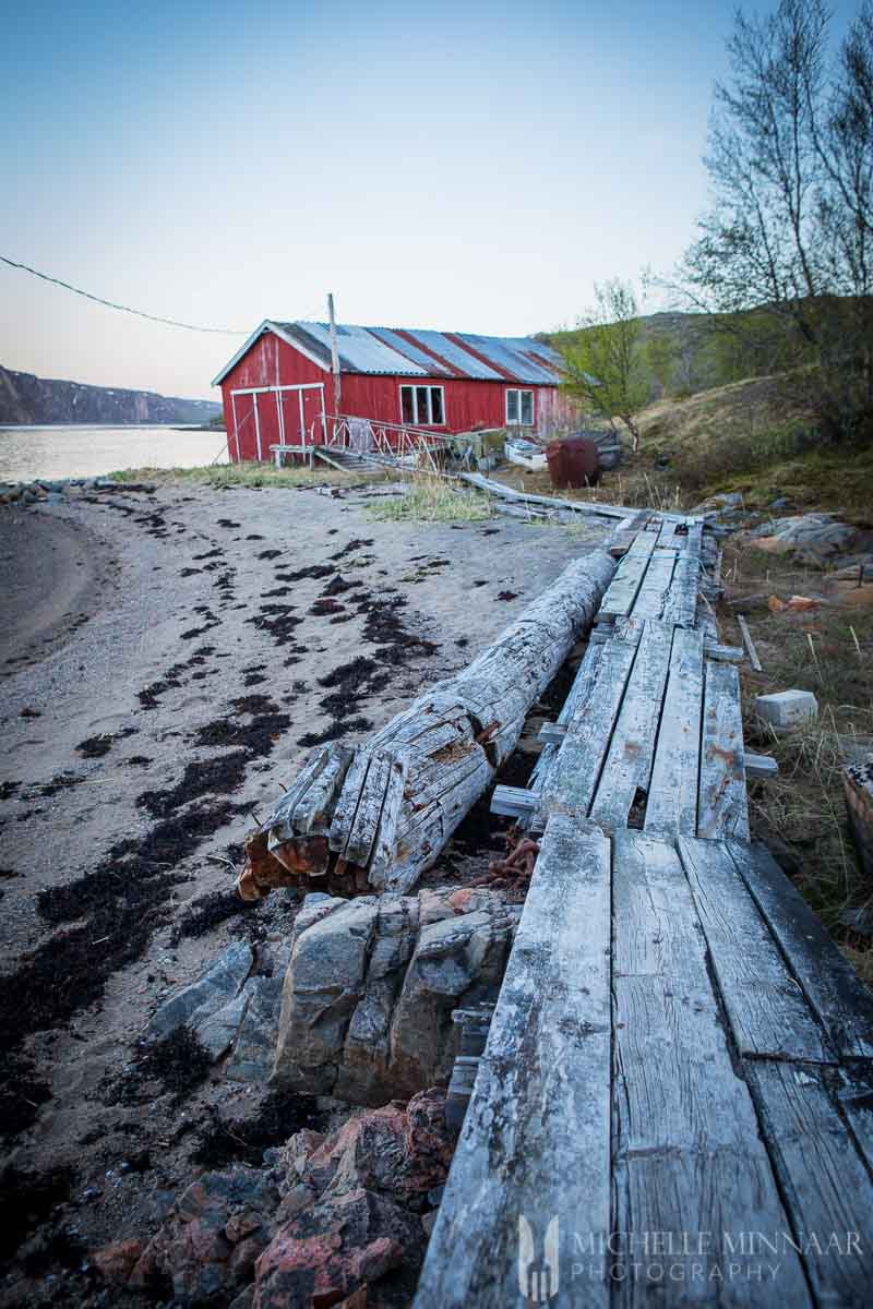 A red barn, sand, trees and a long wooden plank